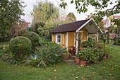 Gartenhaus mit Geranien in Töpfen und Buchs im Beet
