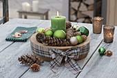 Adventliche Deko mit grüner Kerze, Kugeln und Zapfen in Holz-Schale