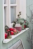 Fensterbank dekoriert mit roten Kugeln, Windlichtern, Zapfen, Moos, Efeu
