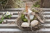 Osternest aus Gras und Moos, Osterei mit Schleife und Feder geschmückt