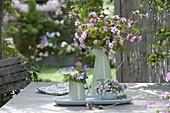 Straeusse aus Geranium (Storchschnabel) auf Gartentisch