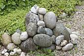 Kieselsteine am Beet gestapelt als Steinskulptur