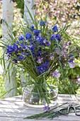 Blauer Stehstrauss aus Aquilegia (Akeleien) und Gräsern in Glasschale