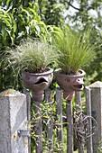 Handgetoepferte Keramik mit Vogelgesichtern auf Zaun , bepflanzt mit Festuca