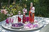 Flaschen mit Rosenlikoer und Rosensirup , Blüten von Rosa (Rosen)