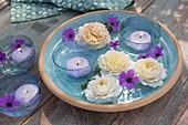 Glas-Schalen mit Schwimmkerzen als Windlichter, Blüten von Rosa