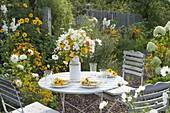Kleiner Sitzplatz am gelb-weissen Beet mit Dahlia 'My Love' (Kaktusdahlie)