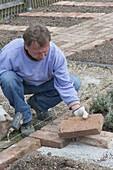 Mann legt Weg aus Klinker und mauert Verkleidung für Wasserleitung