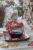 Flasche mit Rotwein-Likör als Geschenk mit Kränzchen aus Hagebutten
