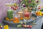 Gläser mit Kerzen als Windlichter auf Metall-Tablett