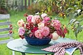 Gesteck in alter Kuchenform mit Rosa (Rosen, Hagebutten) auf Gartentisch