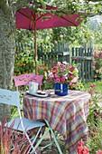Frau deckt Tisch unterm Apfelbaum