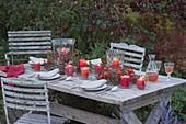 Herbst-Tischdeko mit Windlichtern in Kraenzen aus Zweigen von Rosa