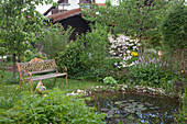 Romantischer Frühlingsgarten mit Bank am Teich