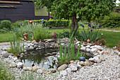 Kleiner Folienteich mit Natursteinen eingefasst im Garten