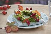 Serviettendeko mit Moos-Kränzchen, Rosa (Hagebutten) und Blättern