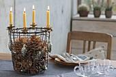 Drahtkorb als 5-Minuten-Adventskranz mit gelben Kerzen, Zapfen