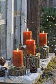 Orangene Kerzen auf Stammstuecken mit Moos, Zapfen und Schlehen