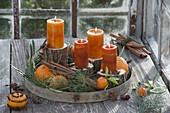 Mediterrane Adventsdeko mit kupferorangen Kerzen auf Stammstuecken