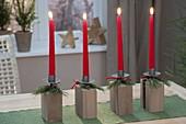 Moderner Adventskranz aus Kerzenhaltern auf Holz-Kloetzen, roten Kerzen