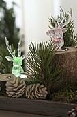 Weihnachtliche Wald-Dekoration mit farbigen LED-Leuchthirschen