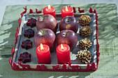 Holz-Untersetzer mit 4 roten Kerzen, Äpfeln (Malus), Zapfen