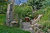 Lauschige kleine Kiesterrasse zwischen Natursteinen, Gräsern und Hydrangea paniculata (Rispenhortensie), Liegesessel und Beistelltisch, geflochtener Gras-Zopf als Deko