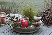 Einmachglas als Windlicht mit roter Kerze in Metall-Schüssel