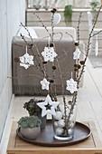 Zweige von Larix (Lärchen-Zweige) in Glasvase mit weissen Baumkugeln