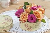 Kleine Blumentorte aus Blüten von Rosa (Rosen) in Keksdose