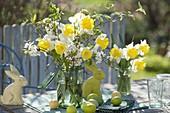 Gelb-weisse Osterstraeusse aus Narcissus (Narzissen) und Zweigen