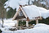 Verschneites Vogelfutterhaus mit Kohlmeise und Grünfink