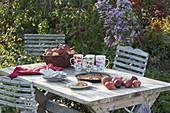 Tisch mit frisch geernteten Äpfeln und Apfel-Tarte