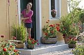 Körbe mit Zinnien und Gräsern am Hauseingang