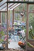 Kleine Terrasse im Gewächshaus, Tisch und Stühle
