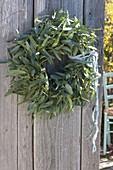 Kranz aus Rückschnitt von Eucalyptus an alter Holztuere