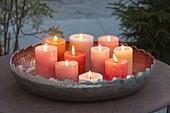 Kerzen in Kupferschale auf Terrassentisch