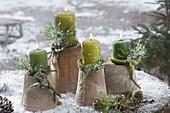Grüne Kerzen auf umgedrehten Terracotta-Toepfen, Zweige von Pinus