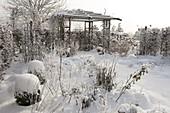Pavillon im verschneiten Garten, Beete mit Stauden