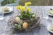 Ostertischdeko mit Kranz aus Zweigen, Gräsern und gelber Primel