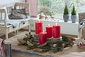 Schlichte Adventsdeko mit roten Kerzen auf Holzscheiben