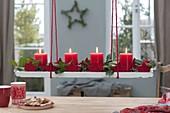 Hängender Adventskranz auf Holzuntersetzer über dem Tisch