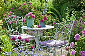 Sitzplatz im Rosengarten zwischen bluehenden Beeten