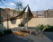 Dachterrasse aus Holz mit Gräsern, Agapanthus, Sonnensegeln, Liege, Tisch und Klappsesseln, fest eingebaute Bank an der Wand entlang