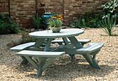 Runde Tisch-Bank-Kombination als Sitzgruppe auf Kiesfläche, Mauer aus Ziegelsteinen