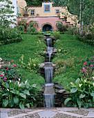 Wasserkaskade durch Wiese entspringt in Grotte am Haus, Zantedeschia in Toepfen , Primula (Schluesselblumen), Farne, Gräser, in Kübeln am Haus : Fritillaria imperialis 'Aurora' (Kaiserkrone), Agaven,