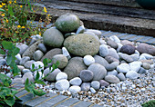 Water Feature: A PILE of Sea WORN PEBBLES AND GRAVEL CREATE A SMALL FOUNTAIN. ROBIN Green & RALPH CADE'S SEASIDE STYLE Garden, LONDON.