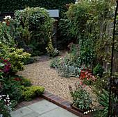 Schmaler Stadtgarten mit Kies, Pflaster, efeuumrankter Laube