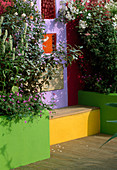 THE SPECSAVERS Garden: CONCRETE RENDERED WALL PAINTED Mauve with COLOURED WINDOWS AND WOODEN BENCH. DESIGNERS NAILA Green AND LEE JACKSON