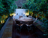 ROOF TERRACE with DECKING at NIGHT: WOODEN TABLE AND CHAIRS, GALVANISED Metal CONTAINERS with BAMBOO, WHITEWASHED WALL :DESIGNED by Wynniatt-HUSEY CLARKE